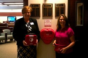Donna Stevens, American Red Cross Health and Safety Account Executive pictured with Vickie Routhier, SVP – Chief Marketing and Sales Officer for Bank of New Hampshire display a Red Cross Automated External Defibrillator (AED) machines. Bank of New Hampshire purchased 22 AED machines for their locations.